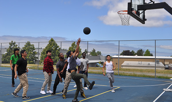 South Seattle College students playing basketball outside blue sky blue court