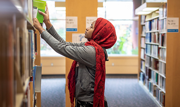 South Seattle College student pulling book in the library